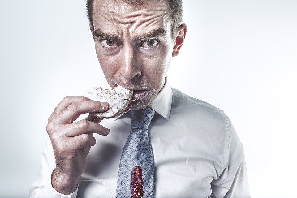 a man eating doughnut with confused facial expression