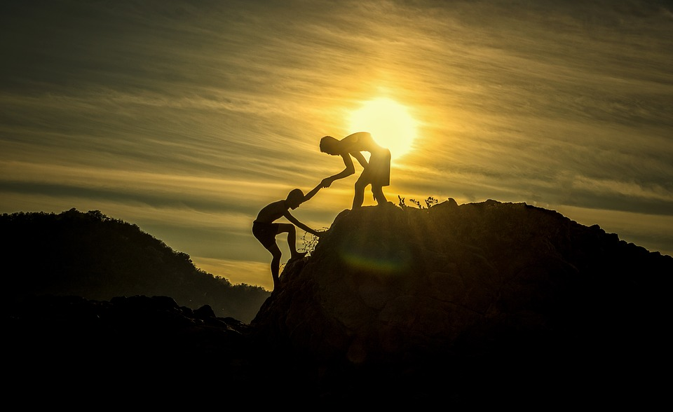 a two man lifting up each other while climbing at the hill under the sunset
