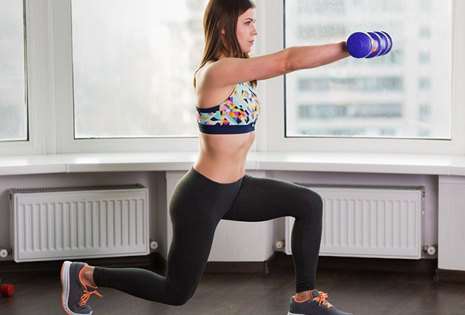 a lady doing the foward lunge while holding the dumbells forward to lose her arm fats