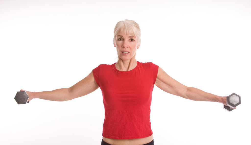 Old lady holding a small size  dumbbells side ward