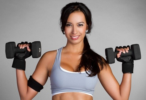 a lady holding a pair of dumbbells